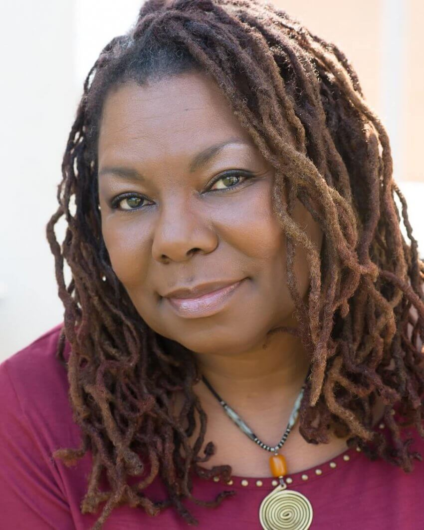 Photograph of Deletta Gillespie, a middle-aged Black woman looking at the camera with a slight smile. She has shoulder-length dreads, and is wearing a necklace of grey and amber beads with above a bronze spiral. She is wearing a raspberry-colored shirt with gold bead edging around the scoop neck.