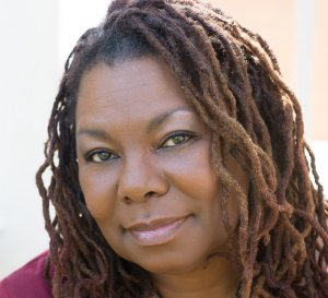 Playwright Deletta Gillespie - a middle-aged Black woman with dreadlocks and a gentle smile