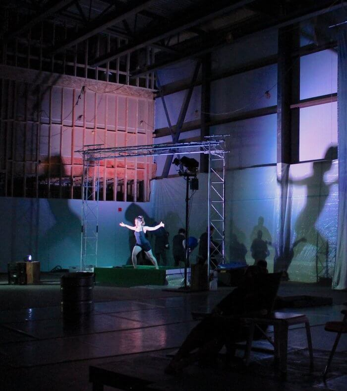 Lunging actress with arms outstretched in large room with colored lights and shadows on walls