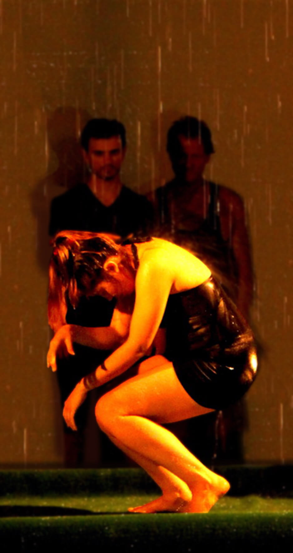 Actress, Ximena Calderón in a black dress crouching as stage rain fall on hers 2 men in back look at her.