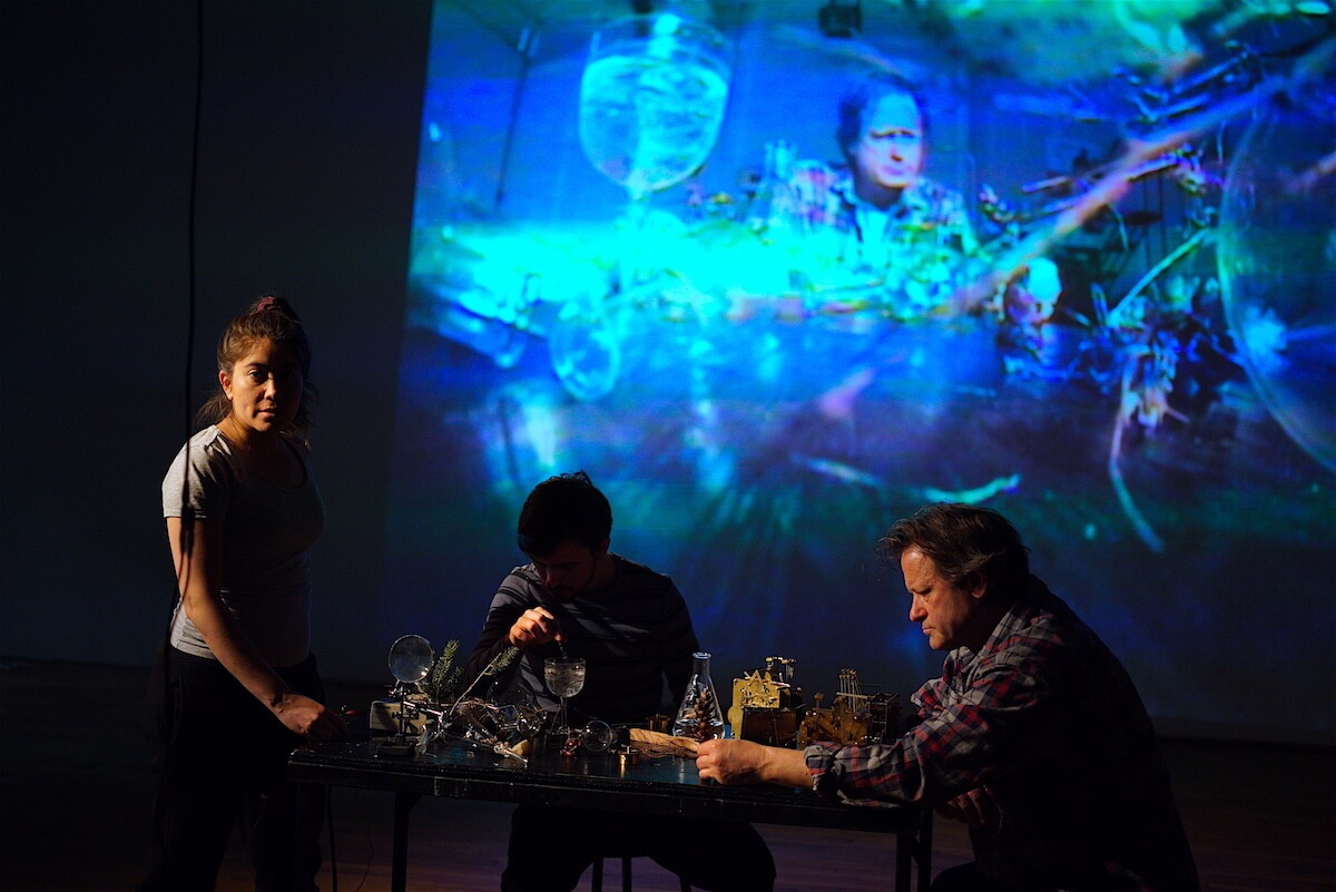 """A rehearsal of Serious Play's """"Moving Water"""" showing 3 actors in front of a projected image in blues, aquas and purples. A wavy, watery image, it shows one of the actors faces at the top of the frame. In front of the projection an actress stands left of a table looking out at us. She is lit from the left side. The rest of her body is shadowed. She is next to a table filled with glass paraphernalia. A man is is seated behind the table in shadow pouring water into a glass. A 3rd man sits at the table opposite the woman. He is lit from the left and we can see that he is reading a piece of paper."""